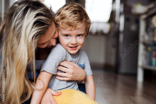 A happy mother with a toddler son indoors at home. Copy space. Fototapet