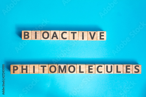 Photo Bioactive phytomolecules inscription wooden cubes with letters on a blue backgro