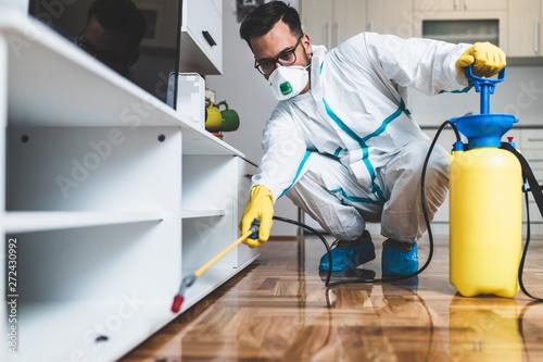 Fotografía  Exterminator in work wear spraying pesticide with sprayer
