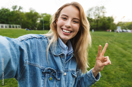 Foto auf Leinwand Texturen Photo of happy smiling woman taking selfie photo and gesturing peace sing while walking in green park