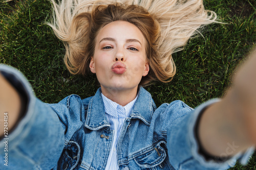 Photo of happy kind woman taking selfie photo and sending kiss while lying green Poster Mural XXL