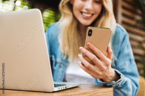 Fotografie, Tablou  Portrait of cute smiling woman using laptop and cellphone in cafe outdoors