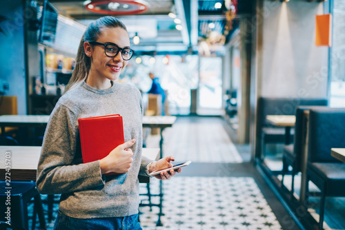Photo  Half length portrait of cheerful female student standing near table at cafeteria