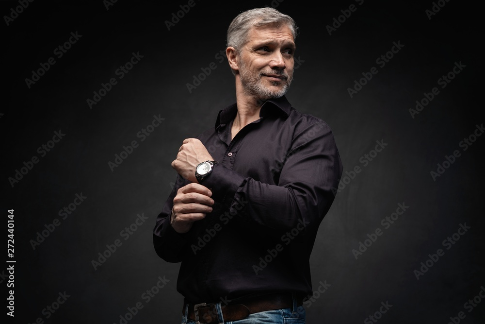 Fototapeta Middle-aged good looking man posing in front of a black background with copy space.
