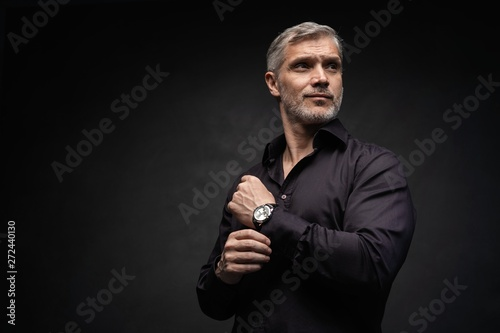 Fotografia  Middle-aged good looking man posing in front of a black background with copy space