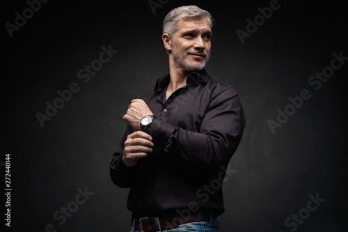 Stampa su Tela  Middle-aged good looking man posing in front of a black background with copy space