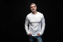 Middle-aged Good Looking Man In White T-shirt Posing In Front Of A Black Background With Copy Space.