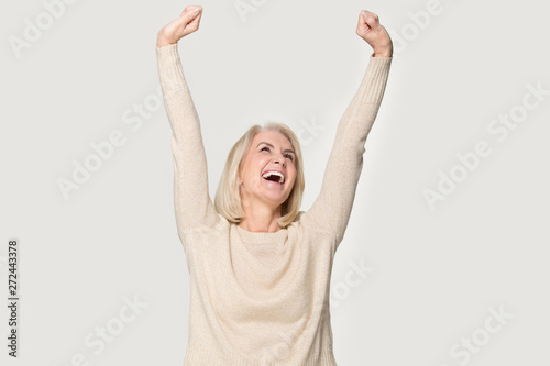 Excited senior woman raised stretched hands feels happy studio shot