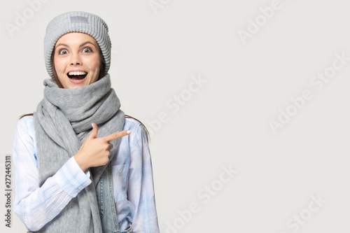 Fotografía  Girl wearing knitted hat warm scarf pointing finger at copyspace