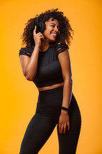 Lifestyle Concept. Portrait Of Beautiful African American Woman With Curly Hair Joyful Listening To Music On Mobile Phone. Yellow Studio Background. Copy Space.