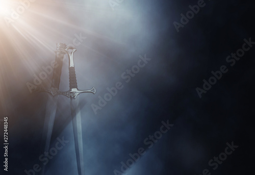 Photo  mysterious and magical photo of silver sword over gothic black background with smoke