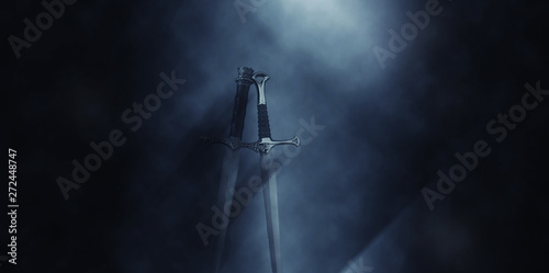 mysterious and magical photo of silver sword over gothic black background with smoke Canvas Print