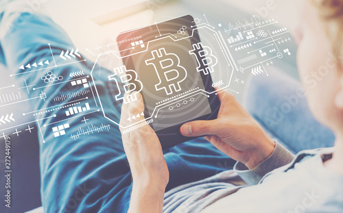 Bitcoin with man using a tablet in a chair