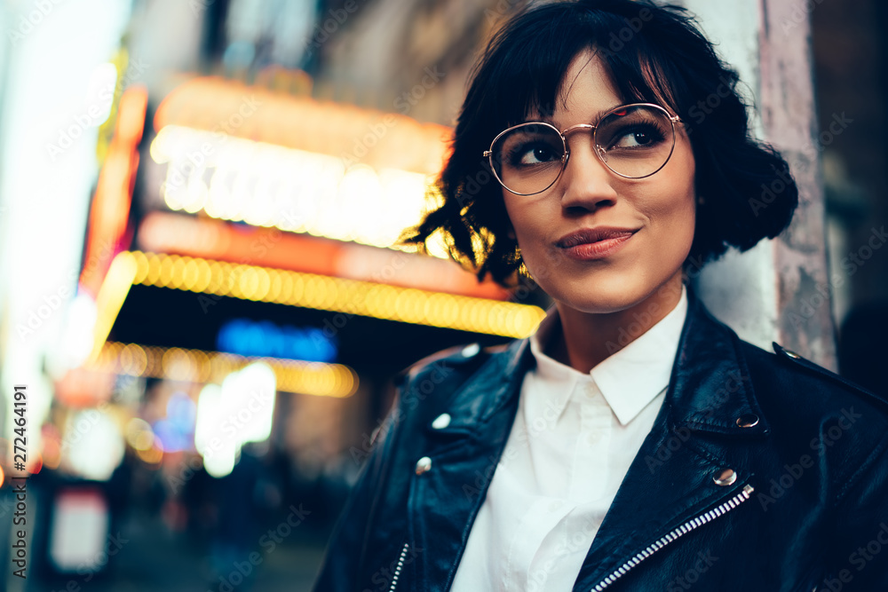 Fototapeta Pretty stylish hipster girl with short haircut looking away walking in New York street with neon lights.Cute fashionable young woman in cool eyewear enjoying nightlife in downtown of metropolis