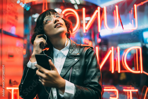 Excited female lover of music dressed in stylish leather jacket listening songs online in earphones connected to smartphone while enjoying night lights and neon illumination in New York City - 272465334