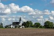 Beautiful, white church in a country, rural setting surrounded by farm fields and trees. Bright blue sky with puffy clouds create a beautiful landscape