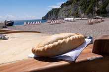 Cornish Pasty On Boat , Beach Location In West Country In Summer With Deck Chairs And Fishing Boat