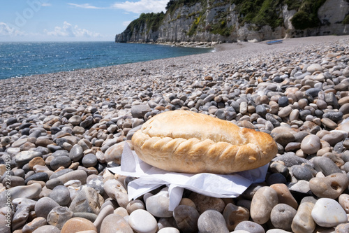 Cornish pasty on shingle beach with sea in background Canvas Print
