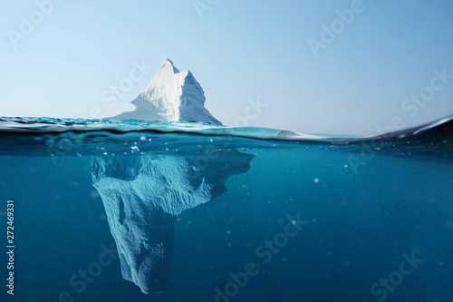 Photo Stands Antarctica Iceberg in the ocean with a view under water. Crystal clear water. Hidden Danger And Global Warming Concept