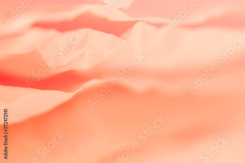 Closeup of pale coral red paper layers stack. Blur abstract art background. Delicate silk texture effect. Copy space.