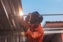Worker Welding In Orange Work Clothes Welding For Roof Truss