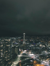 Seattle Skyline At Night With Dark Storm Clouds In Distance