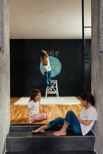 Young Girls Drawing Planet Earth On A Blackboard