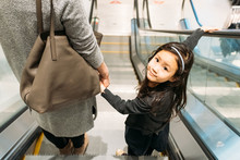Mother And Daughter Moving Escalator In Shopping Mall