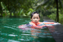 Cute Asian Girl Playing In An Infinity Pool With Mandala Scarves In The Woods Of Nature