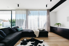 Large Charcoal Sofa In A Luxury Living Room With Sheers