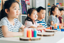Preschool Kids Painting In Classroom