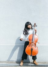 Portraits Of Female Jazz Cellist Playing In Outdoor Space