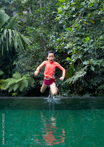 Asian children diving in swimming pool in natural woods