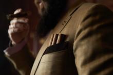 Beard Man Holding Cigars In His Pocket.