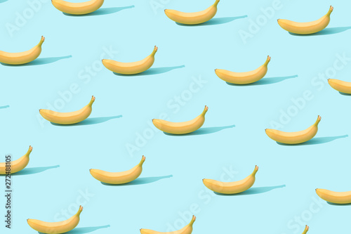 Trendy sunlight Summer pattern made with fresh banana fruit on bright light blue background. Minimal summer concept. - 272488105