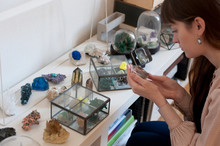 Woman Examines One Crystal From The Collection Of Minerals