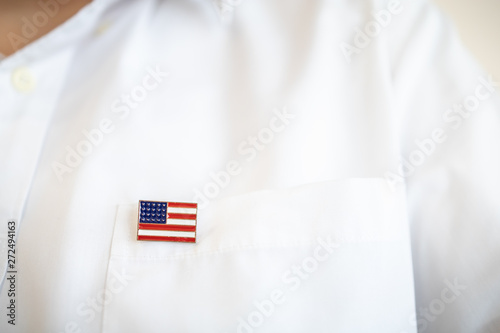 Photo  Close up of United State of America pin national flag on white shirt pocket