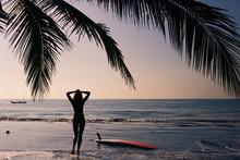 Woman Walking Along The Beach At Sunset