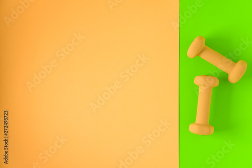 Fitness equipment with womens yellow weights/ dumbbells isolated on a lime green and yellow background with copyspace