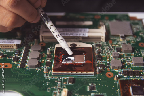 Technician applying thermal paste with syringe on the CPU