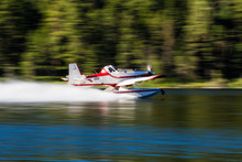 A Forest Fire Fighting Floatplane Skimming On The Surface Of A Lake To Fill It's Tanks