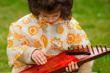 Central Park Of The City. A Young Child Is Playing The Gusli, Psaltery -ancient Traditional Russian Folk Instrument. Horizontal View.
