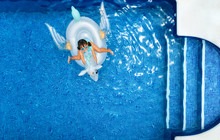 Little Girl On A Unicorn Shaped Float In A Swimming Pool