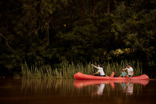 Family Paddling Red Canoe In T...