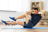 sport, fitness and healthy lifestyle concept - man making bicycle crunch on exercise mat and flexing abs at home