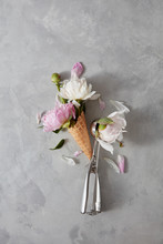 Beautiful Flowers White And Pink Peonies With A Spoon Of Ice Cream And A Waffle Cup On A Ligt Gray Background.