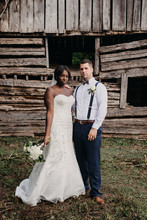 Wedding Couple Posed In Front Of Rustic Structure