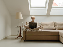 Woman In Cozy Mansard Room Using Laptop On Couch
