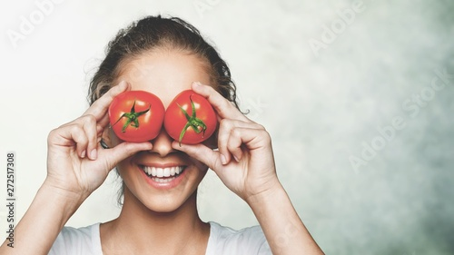 Beautiful laughing woman holding two ripe tomatoes - 272517308
