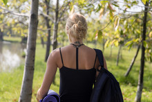 Woman Walking With Yoga Mat In A Park
